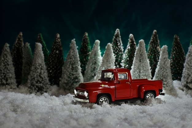 A toy red chevrolet pickup truck carries a christmas tree in the forest