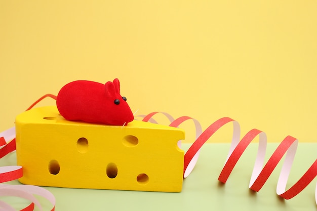 Toy red mouse on toy yellow cheese. mouse-symbol of new year 2020.