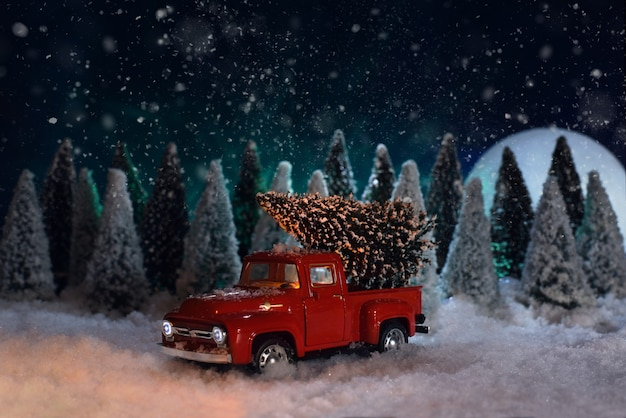 Toy red pickup truck carries a christmas tree in the forest