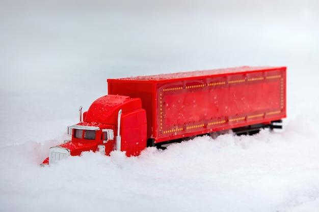 おもちゃの赤いトラックが新年とクリスマスの贈り物をもたらします冬の休日が来ています本物の雪の吹きだまりに乗ります