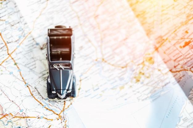 Toy retro cabrio car on the map, tourism concept