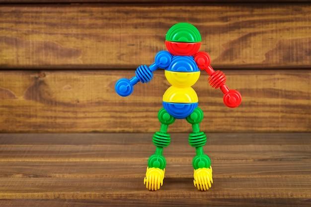 나무 배경에 장난감 플라스틱 다채로운 세부 사항으로 만든 장난감 로봇