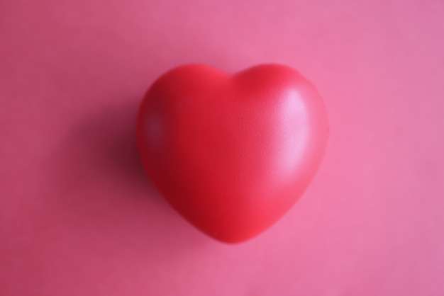 Toy rubber heart lying on red background closeup top view