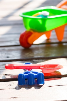 Toy sand pails and shovels over on wooden terrace on sunny day