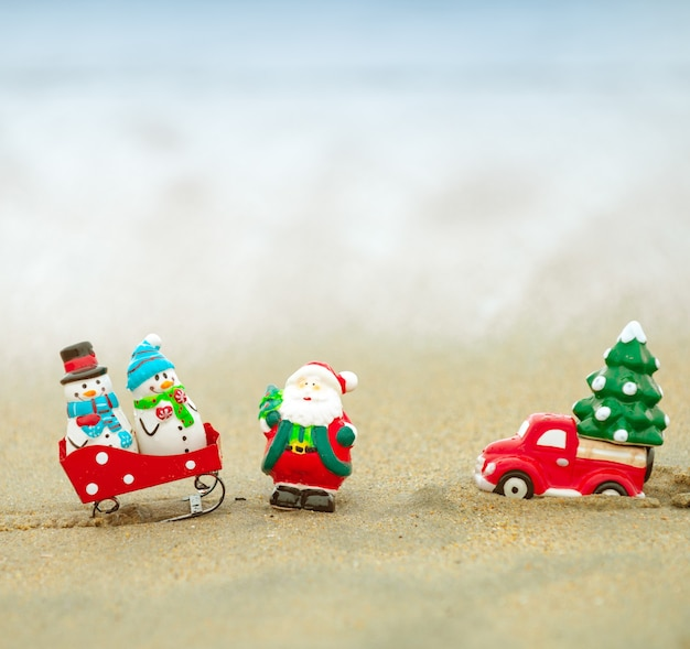 Toy santa claus against tropical ocean background. christmas in hot vacation. warm new year climate, theme for posters, greeting cards.