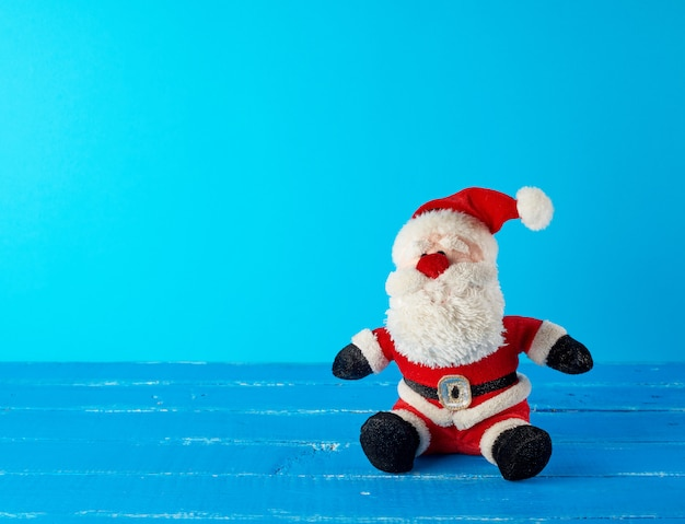 Toy santa claus in a red suit sitting