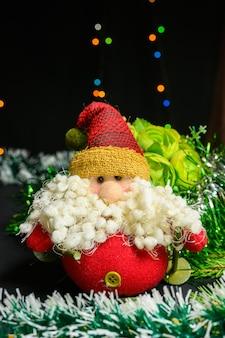 Игрушечный дед мороз с большой бородой на фоне гирлянды и цветов. рождество и новый год концепция на черном фоне.