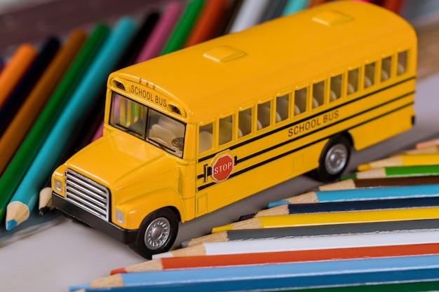 Toy school bus with color wooden pencils.