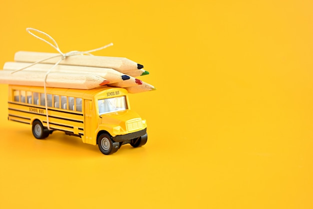 Toy school bus with pencils on the roof.