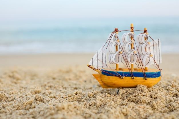 海沿いの砂の上におもちゃの船。夏休みのコンセプト