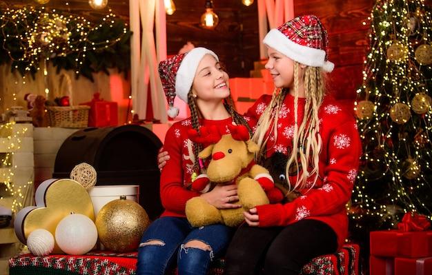 장난감 가게. 작은 소녀는 크리스마스 분위기가 있습니다. 새해 복 많이 받으세요. 자매는 가족 휴가를 함께 보냅니다. 산타 어린이 장난감 곰. 겨울 쇼핑 판매 아이 스토어. 크리스마스 파티 시간입니다. 해피 홀리데이.