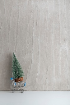 Toy shopping cart and small artificial christmas tree. buying christmas tree. copy space. vertical frame.