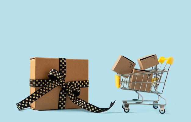 Игрушечная тележка для покупок с коробками и кредитной картой на синем фоне копирует пространство для продажи текста или дизайна