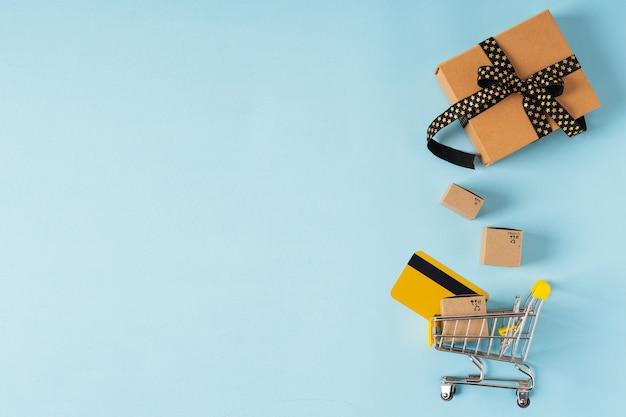 Магазинная тележкаа игрушки с коробками и кредитной картой на синем фоне. скопируйте место для текста или дизайна. распродажа