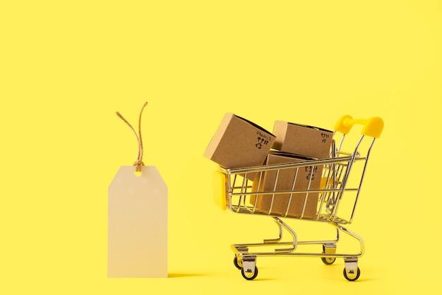 Игрушечная тележка для покупок с коробками и пустой биркой на желтом фоне