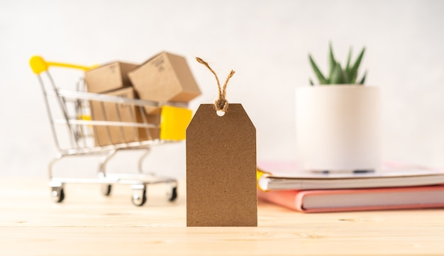 Toy shopping cart with boxes and empty blank tag, succulent plant and notepad.
