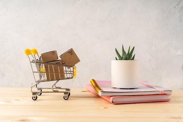 美しいサボテンとコンクリートの鉢に植えられた木製の机の上に箱が付いたおもちゃのショッピングカート。灰色の壁。ショッピングのコンセプト。
