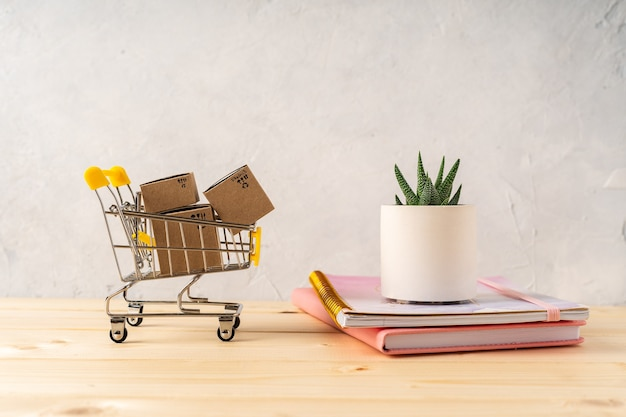 Toy shopping cart with boxes on the wooden desk with beautiful cacti and plant in concrete pots. gray walls. shopping concept.