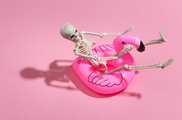 ピンクの明るい上に膨脹可能なフラミンゴが付いているおもちゃの骨格。ハロウィーンのテーマ。ビーチでの休暇のコンセプト。夏休み。