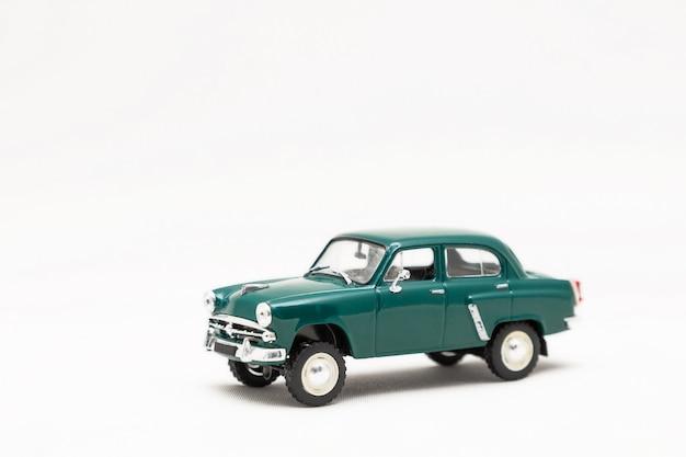 白い背景の上のレトロな車のおもちゃの小さなモデルは分離します