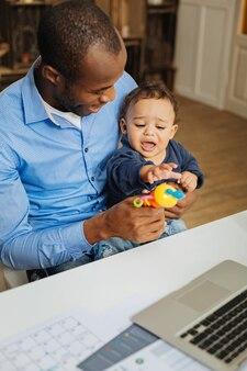 おもちゃ。彼のラップトップでテーブルに座っている間彼の幼い息子と彼のおもちゃを保持している愛情のある若いアフリカ系アメリカ人のお父さんの笑顔