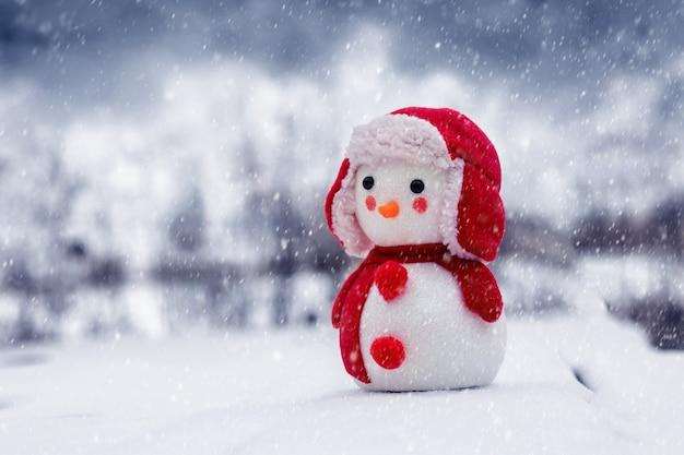 Игрушечный снеговик в поле во время снегопада. снеговик - символ рождества и нового года