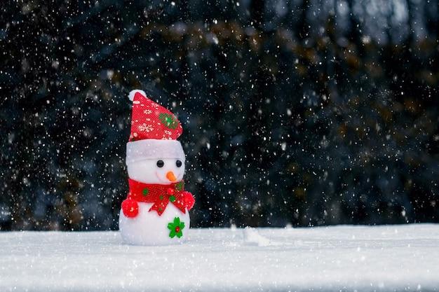 降雪時に暗い背景の森の中でおもちゃの雪だるま