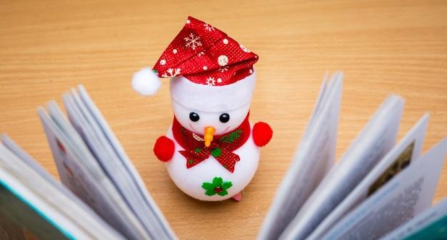 展開された本の近くのおもちゃの雪だるま。フィクションを読んだり、面白い本を読んだりする_