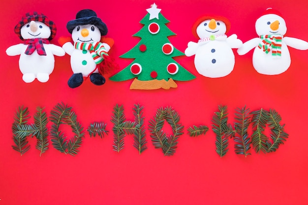 Toy snowmen and christmas tree near inscription