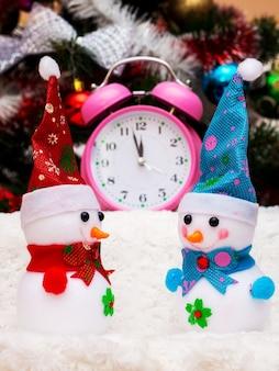 新年の12時間の接近を示す時計の背景におもちゃの雪だるま。雪だるま、クリスマスツリーの近くの時計_