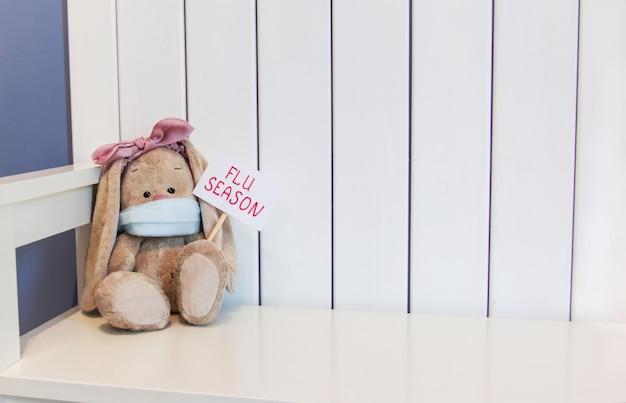 Мягкий игрушечный кролик сидит в маске и держит знак сезона гриппа