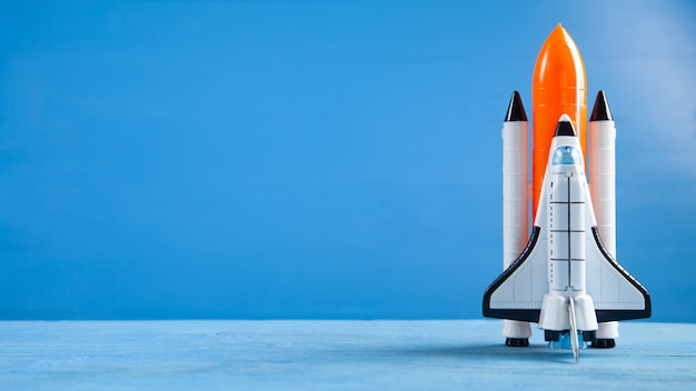 Toy space shuttle on blue background. rocket launch