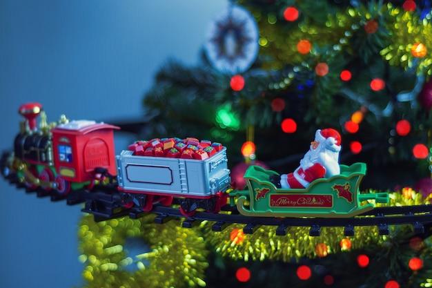 ボケの光の花輪の背景に飾られたクリスマスツリーのおもちゃの蒸気機関車