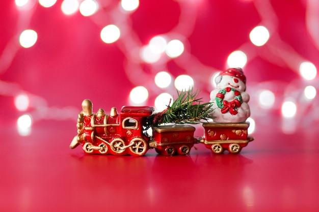 크리스마스 트리와 bokeh와 빨간색 배경에 눈사람 장난감 증기 기차. 가로 사진