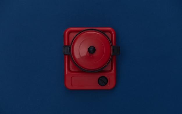 Игрушечная плита и сковорода на классическом синем фоне. цвет 2020
