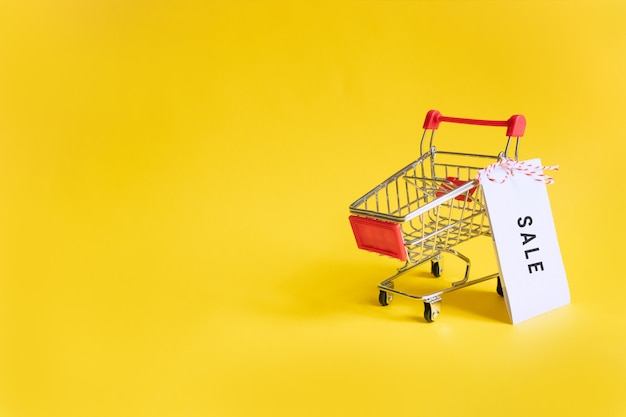 Toy supermarket cart with sale sticker on a yellow .  sales, shopping and black friday. copyspace for text.
