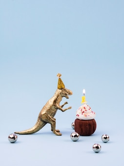 Toy t-rex and little birthday dessert