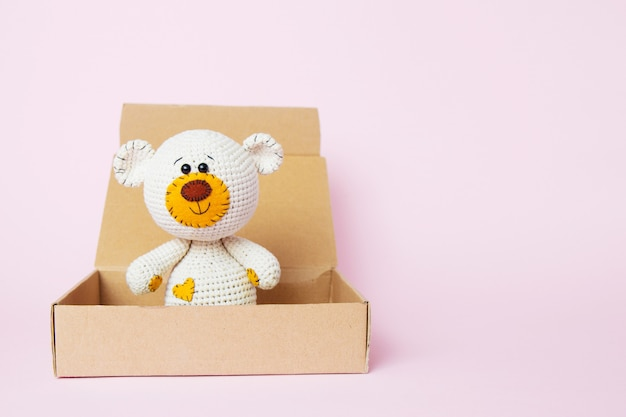 Toy teddy bear in a craft box isolated on a pink background. baby background. copy space, top view