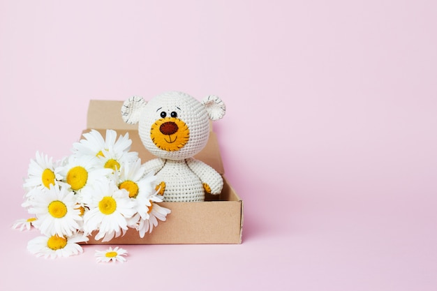 Toy teddy bear in a craft box with daisies isolated on a pink background. baby background. copy space, top view