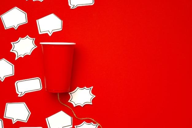플라스틱 컵과 연설 거품 빨간색 표면에 문자열로 만든 장난감 전화
