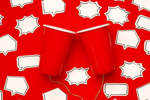 プラスチック製のコップと吹き出し付きの赤の文字列で作られたおもちゃの電話
