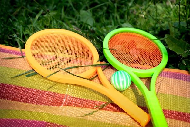 カラフルな縞模様の毛布の上にボールが横たわっているおもちゃのテニスラケットが草の上に広がっています