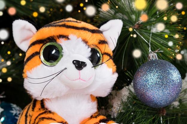 크리스마스 트리 배경에 있는 장난감 호랑이.