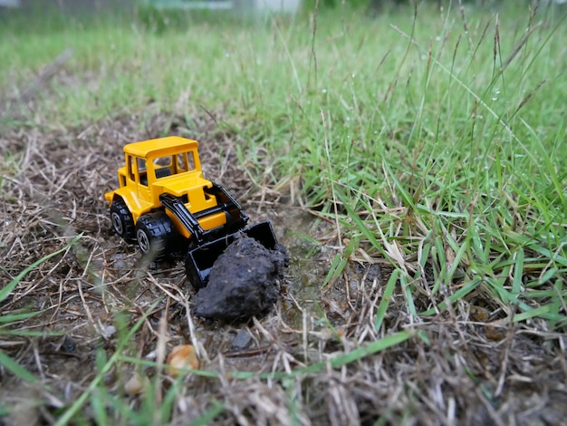 Toy tractor on soil. model of the tractor on the soil. tractor on the soil