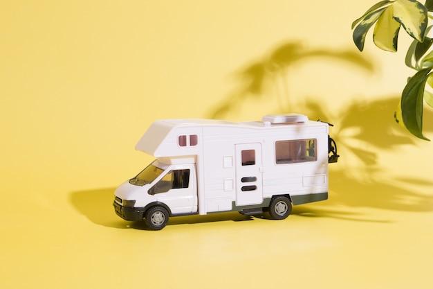 Игрушечный фургон на желтом фоне с тенью растений. минималистичная концепция летнего семейного путешествия