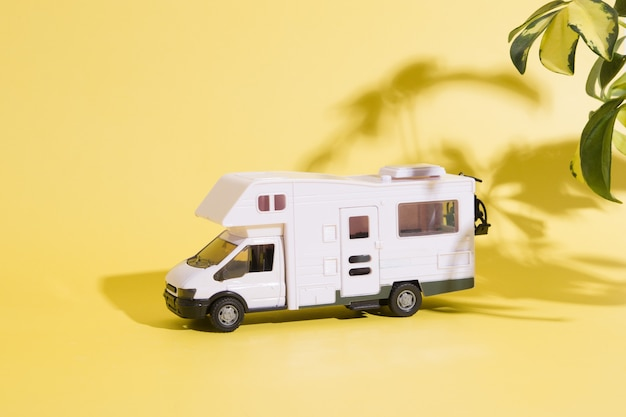 Toy travel van on yellow background with plants shadow. minimalistic summer family travel concept