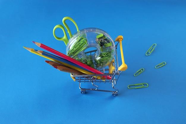 学校に戻るの明るい背景の上面図の概念に文房具とおもちゃのトロリー