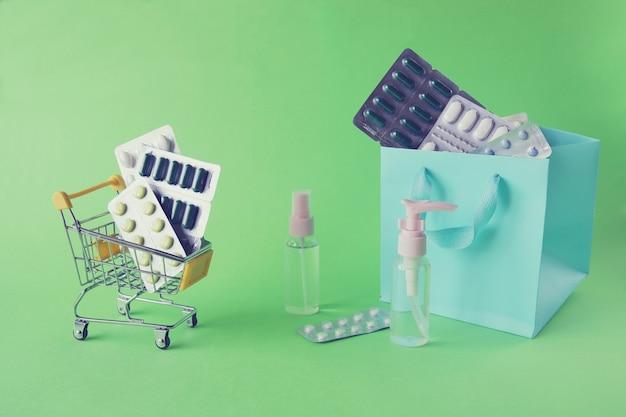 Игрушечная тележка с распылителем различных таблеток и капсул на ярком фоне с копией пространства