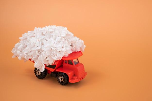 오렌지색 장난감 트럭, 색깔 있는 배경에 흰색 라일락 적재