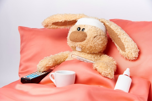 A toy unhealthy rabbit with mediciner and a tv remote control in bed.